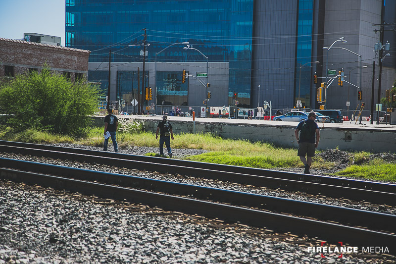 3 team members following tracks in the gravel along a railroad line in downtown Tucson.